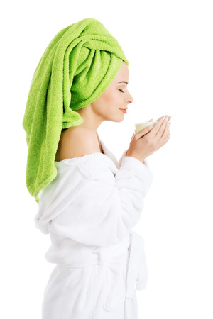 Beautiful woman in bathrobe and turban smelling body lotion  Isolated on white   photo
