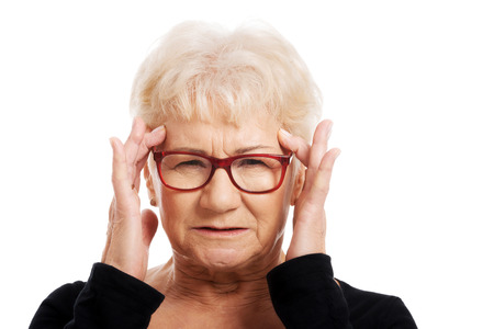 An old woman is eye glasses is having a headache  Isolated on white   photo
