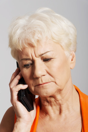 An old lady talking through phone She is receiving bad news  Over grey background  Stock Photo