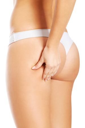 Young woman is touching her skin on buttock to check its supple. Isolated on white.  photo
