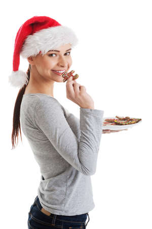 Beautiful woman in santa hat eating a cookie  Isolated on white   photo