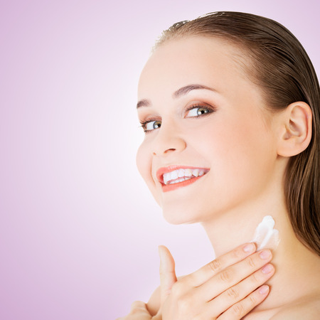 Beautiful woman with healthy skin applying cosmetic cream on a clean fresh face  photo