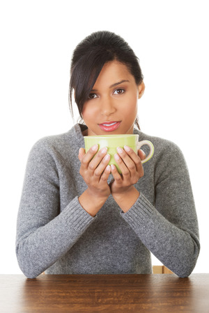 Young woman drinking something from big mug, isolated on white photo