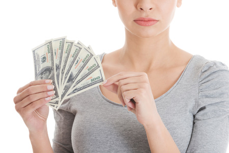 Young beautiful casual woman holding large sum of money. isolated on white. photo