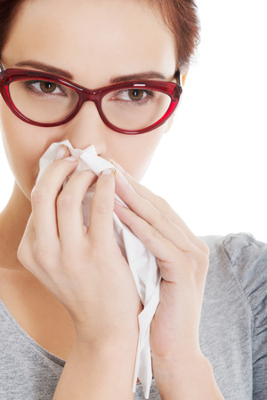 runny: Young beautiful woman having runny nose, with tissue. Isolated on white. Stock Photo