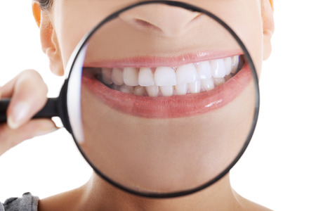 Beautiful woman with magnifying glass showing her perfect white teeth. Over white background. photo