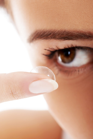contact lenses: Close up on woman putting lens into eye. Over white background.