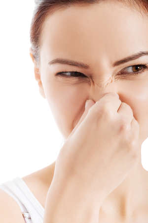 hyperhidrosis: Beautiful woman with grimace beacuse of bad smell. Isolated on white.