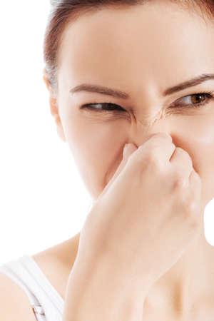 smell: Hermosa mujer con una mueca por culpa de mal olor. Aislado en blanco.