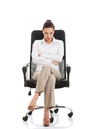 Young sad business woman sitting on a chair. Isolated on white.  Stock Photo - 27968954
