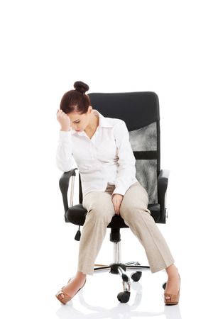 broken chair: Young beautiful business woman sitting on a chair and looking tired, broken. Isolated on white.