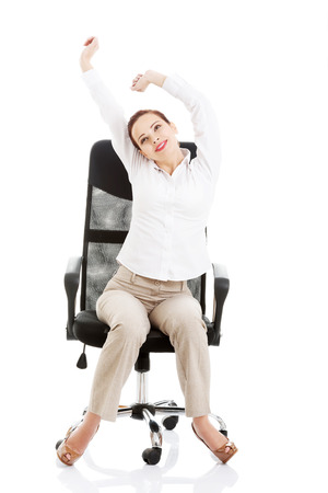 Beautiful business woman sitting and relaxing on a chair. Isolated on white. photo