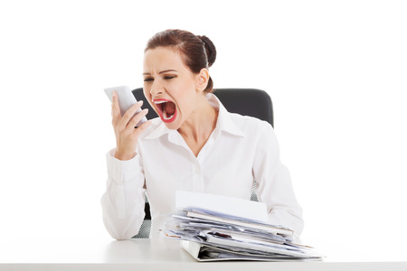 Beautiful business woman sitting, screaming to a phone and has a stack of papers on desk. Isolated on white. photo