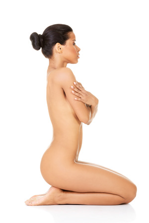 Attractive naked woman sitting on knees. Side view. isolated on white.  photo