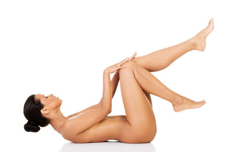 Naked attractive woman lying on her back with legs up. Isolated on white.  photo