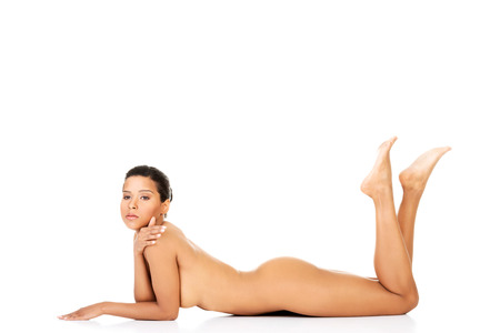 Beautiful naked woman lying with legs up. Isolated on white.  photo