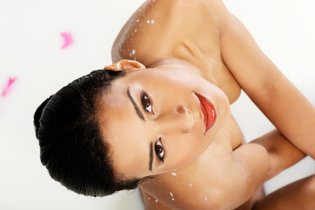 Attractive naked woman lying in a milk-bath with rose petal. Up front view. Closeup.  photo
