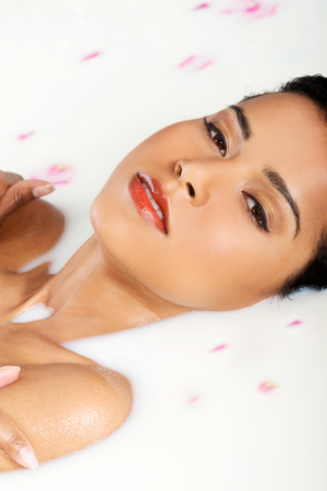 Attractive naked woman lying in a milk bath. With rose petal. Up front view. photo