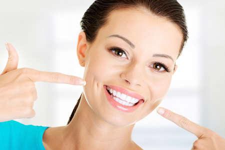 muela: Mujer mostrando sus perfectos dientes blancos y rectos. Foto de archivo