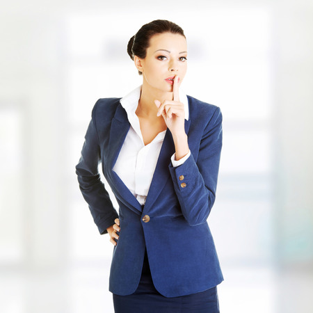 Portrait of attractive business woman with finger on lips, gesturing for quiet  photo