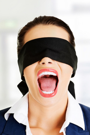 disoriented: Portrait of a beautiful frighten young blindfold woman screaming  Stock Photo