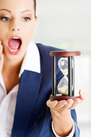 Young shocked business woman with hourglass - time concept  photo