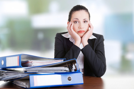 Sad woman with ringbinders sitting at the desk. Tired and exhousted business woman.  photo
