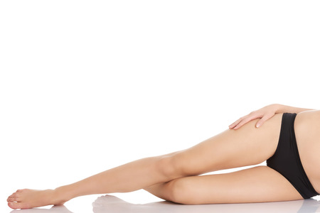 Beautiful woman is presenting her smooth shaved legs. Isolated on white. photo