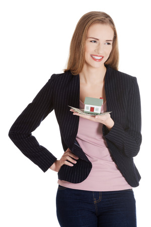 Beautiful business woman holding small house on palm. Isolated on white. photo