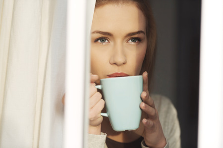 coffee mug: Beautiful caucasian woman drinking hot coffee or tea and looking through window. Indoor background.