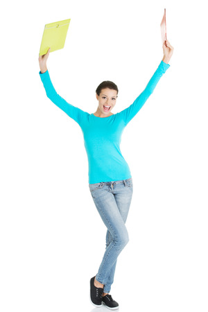 Happy student woman with notebooks showing win gestur, isoalted on white background  photo