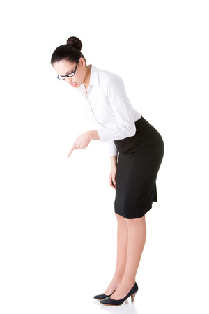 face down: Young business woman bending down and looking. Isolated on white. Stock Photo