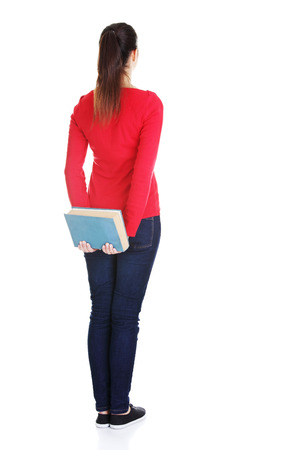 Back view of young student woman holding an old book. Isolated over white background. photo