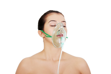 oxygen: Diseased female patient wearing a oxygen mask against white background