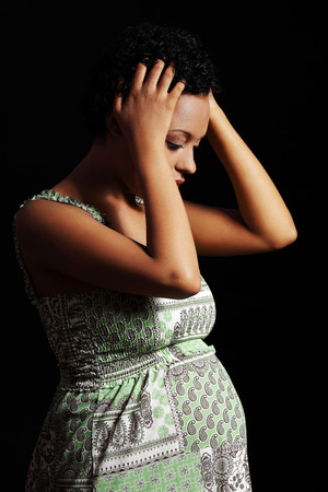 Depression and stress of young pregnant woman against black background  photo