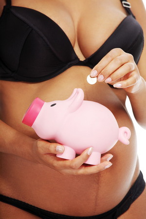 Young beautiful pregnant woman holding a pink piggybank in front of her belly, over a white background.  photo