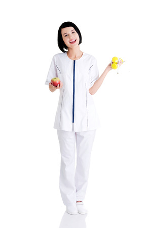 Woman dietitian holding apple and dumbbells with measuring tape  photo