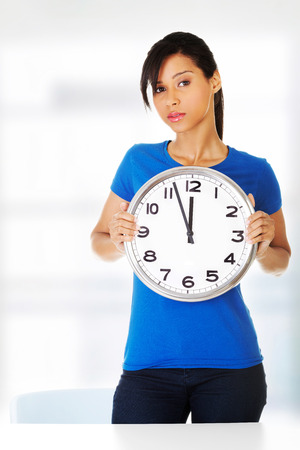 Portrait of shocked woman with clock over white background photo