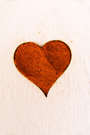 Heart shape made from spice on a wooden spoon. Composition. photo