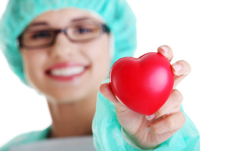 Smiling female doctor or nurse in surgical clothes holding red heart  photo