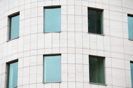 commercial real estate: View on a building for offices, with greeny windows. Part of the building.