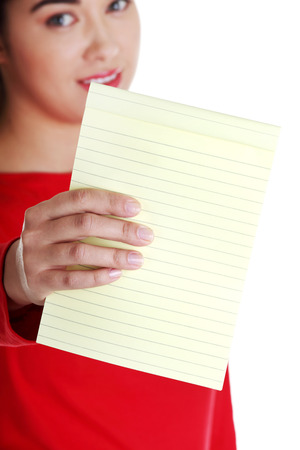 Young happy student woman showing blank notepad, isolated on white background  photo