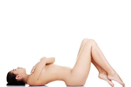 Sexy fit naked woman with healthy clean skin lying down, isolated on white  photo