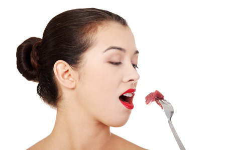 Young beautiful woman eating raw meat. Isolated on white