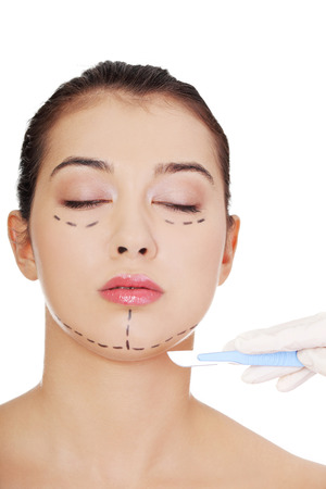 Cosmetic surgery concept. Female face in background of scalpel.  photo