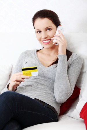 Beautiful woman is holding credit card and talking to the phone, shopping on the phone concept. Indoor. photo