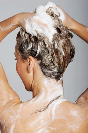 Woman taking a shower and shampooing her hair photo