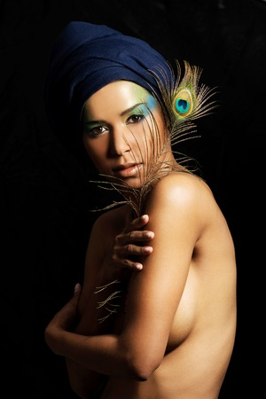 Beautiful woman with  professional make-up with peacock feather photo