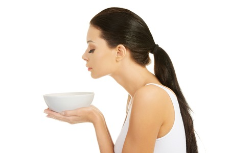 smells: Beautiful young woman holding bowl and smells Stock Photo