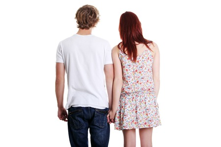 hold hands: Young couple are standing a back side and holding hands.